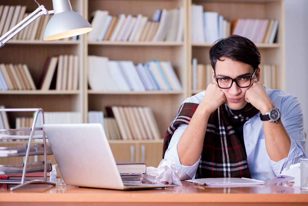 challenges by a freelancer - a frustrated man sitting on his desk with his laptop and books open