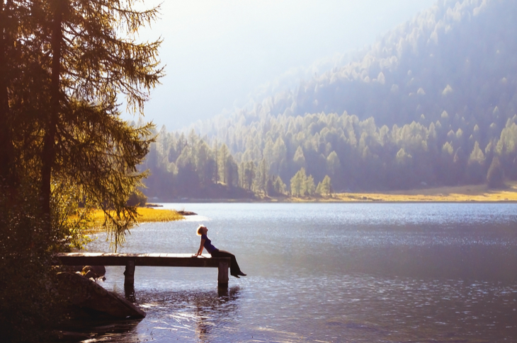 writing - a person sitting and viewing the scenery by the lake