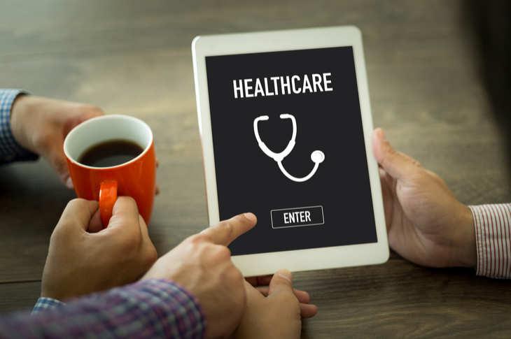 """Man pointing towards the enter button on a tablet that mentions """"HEALTHCARE"""" - Content Marketing Healthcare Industry - Scatter"""