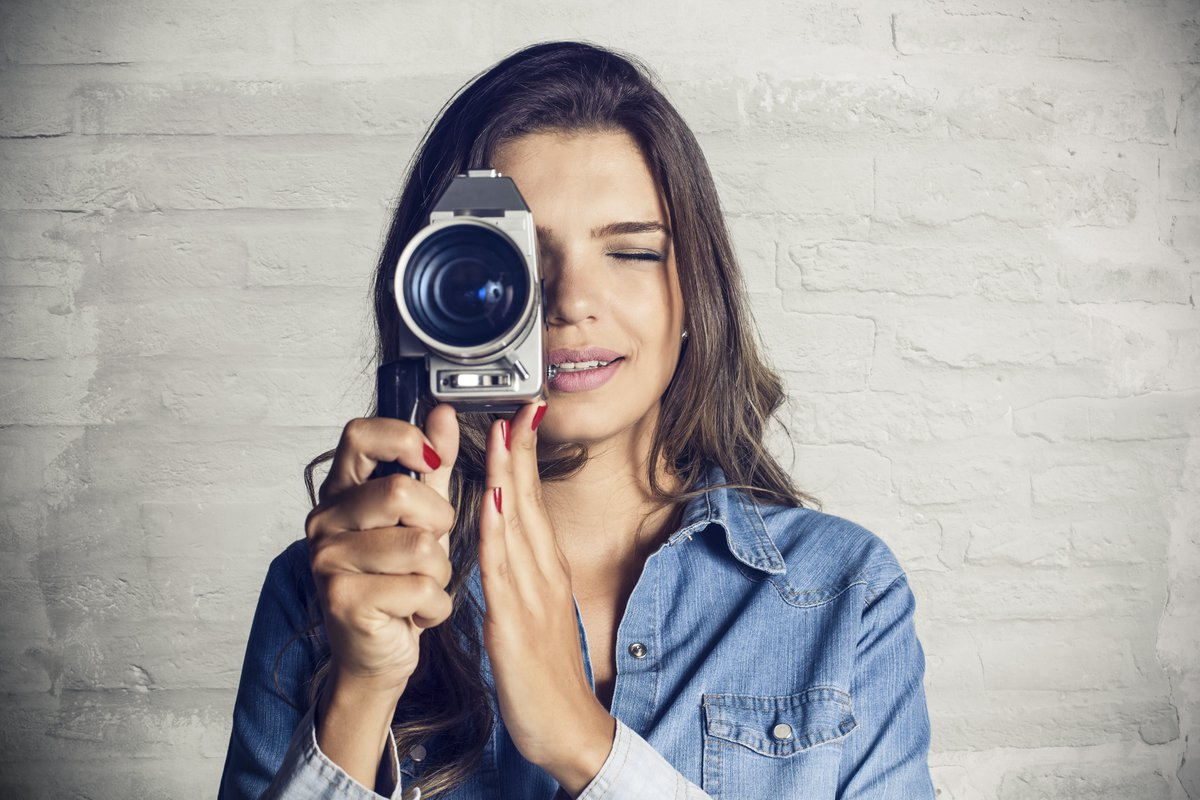 Short Videos - Young adult woman using a handycam to record a video