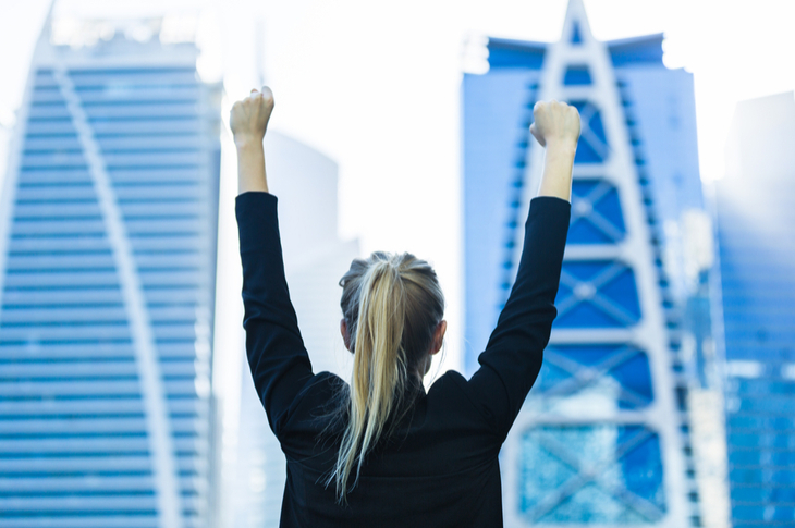 Back view of a business woman standing and stretching her arms while looking at skyscrapers- Content marketing Practices - Small Business Success - Scatter - Influencer Marketing