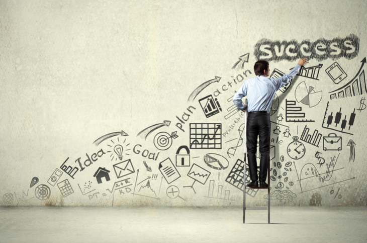 Back view of a businessman drawing a sketch on wall - Content Marketing - Essentials - Scatter