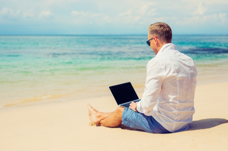 freelancing - a man working on a laptop in the beach