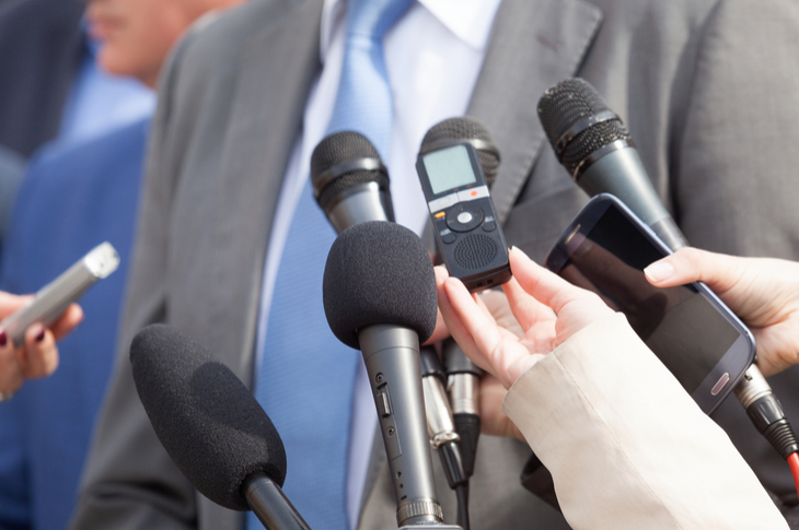 journalism - the media holding mics towards a businessman
