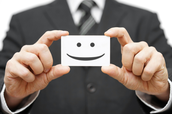 Clients - A businessman holding a card with a smiley face printed - Scatter