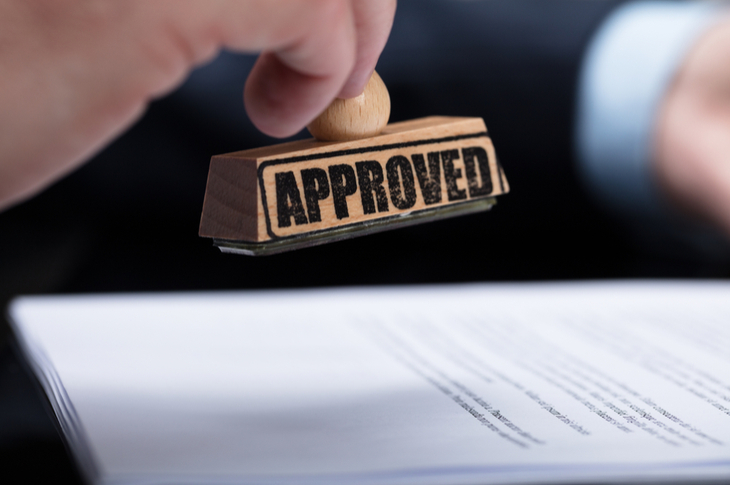 hand stamping approval indicating compliance team's agreement