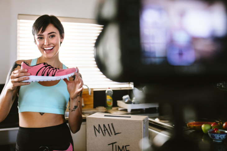 female sports influencer shooting in front of a camera. She has a pink shoe in her hand while she happily smiles.