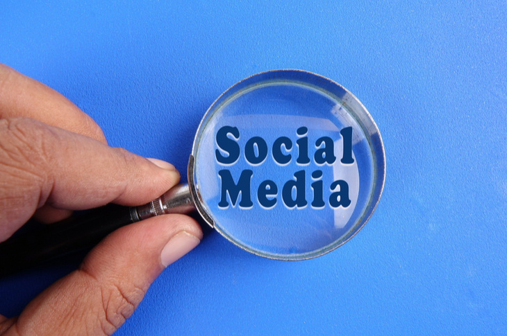 hand holding magnifying glass to conduct social media audit