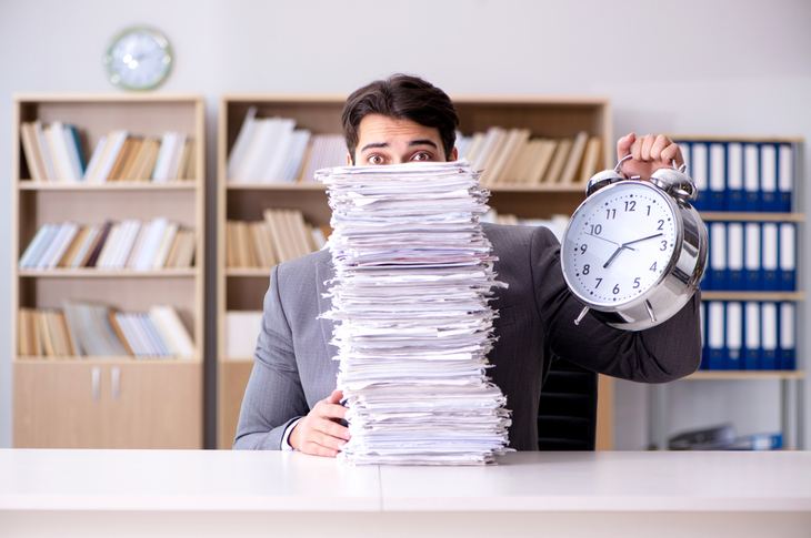 man behind pile of documents holding up clock trying to meet marketing timelines
