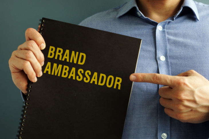Influencer Marketing - Why brands need a long term influencer relationship. He is holding a black notebook with one hand and pointing a finger from his other hand towards it. The book reads Brand Ambassador.