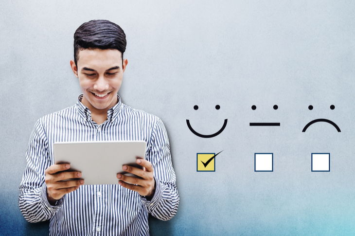 Customer Feedback Concept, Happy Businessman holding digital Tablet with a checked box on Excellent Smiley Face Rating for a Satisfaction Survey - Image