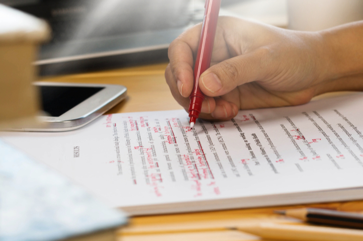 Hand holding red pen over proofreading text in office : editing hacks concept