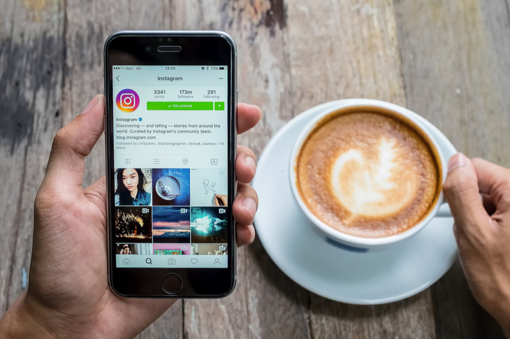 Instagram for Business - A women holds Apple iPhone 6S with Instagram application on the screen - Scatter