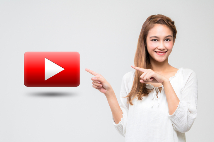young girl pointing at a movie playback button. Concept - Youtube Trends