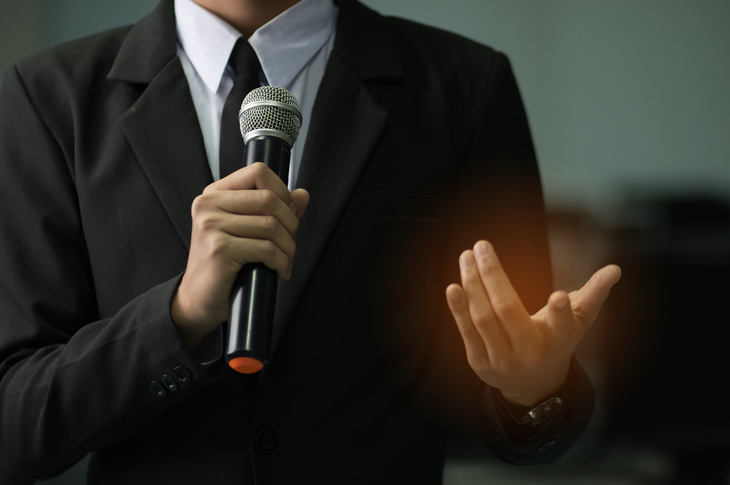 smart businessman speech concept, talking with microphone in conference hall keynote speaker concept